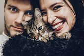 Happy Stylish Hipster Family Hugging With Their Cat. Man And Woman Holding Kitty And Having Fun And poster
