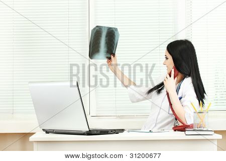 beautiful girl doctor holding X-ray in the office