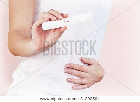 Positive pregnancy test result, closeup on pregnant belly, healthy mother touching tummy, female hand hold medical hormone test, isolated, new life and new family concept