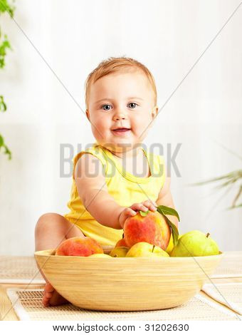 Little baby holding fresh fruits, closeup portrait, concept of health care ans organic child nutrition