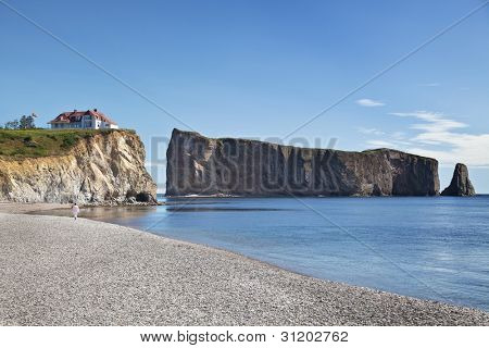 House on a cliff besides a rocky beach and Perce Rock in the Gaspe, Quebec, Canada