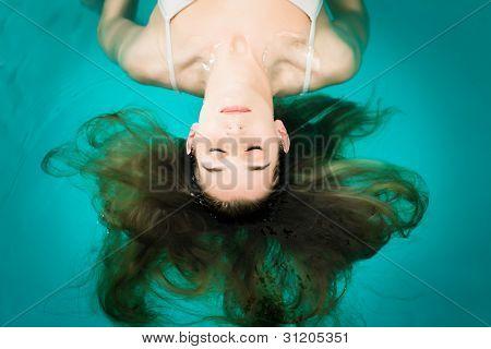 Wellness - mujer joven flotando en el Spa o la piscina, ella es muy relajada