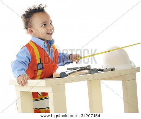 "A preschool ""construction worker"" looking up to the other end of the measuring tape he holds over his workbench.  On a white background."