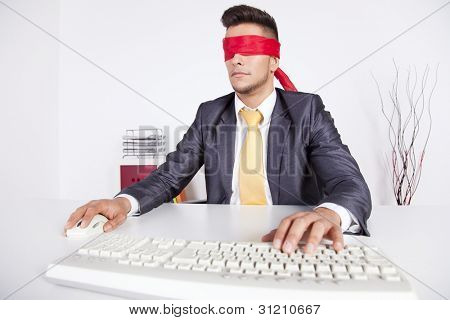 Businessman at his office with scarf covering his eyes while working with his computer