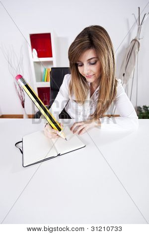 Businesswoman taking some notes on her notepad with a giant pencil