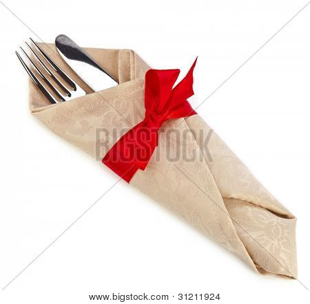 cutlery and napkin with red ribbon bow isolated on white