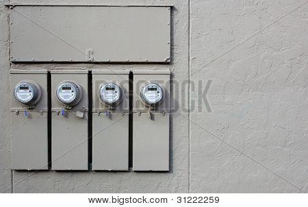 Diez metros eléctricos en la pared de estuco gris de un edificio de apartamentos