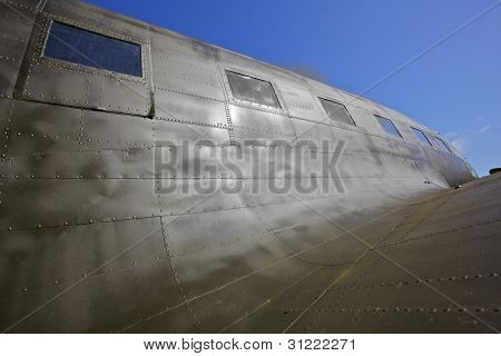 WW II transport airplane, the C-47 showing dramatic contours with blue sky background