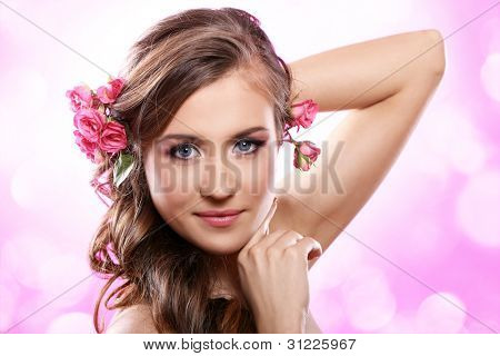 Beautiful woman with roses in hair over pink background