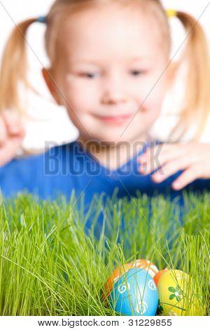 Cute little girl found Easter eggs hidden in a grass
