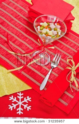 Beautifully decorated portion of Russian salad stands on the hol