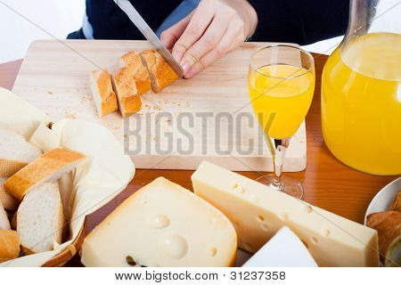 Table With Food And Female Hands Cutting Bread