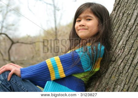 Adorable Little Girl Sitting In Tree