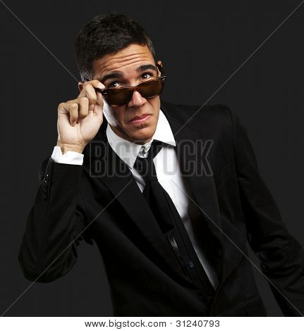 portrait of business man taking off the sunglasses against a black background