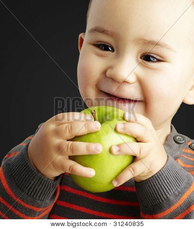 portrait of funny kid holding green apple and smiling over black
