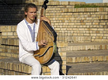 Kiev, Ukraine - August 24: Street Musician On The Street, Playing On An Old Natsyonal Stringed Tool