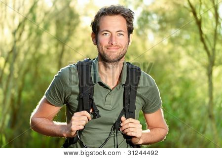 Young man hiking smiling happy portrait. Male hiker walking in forest.