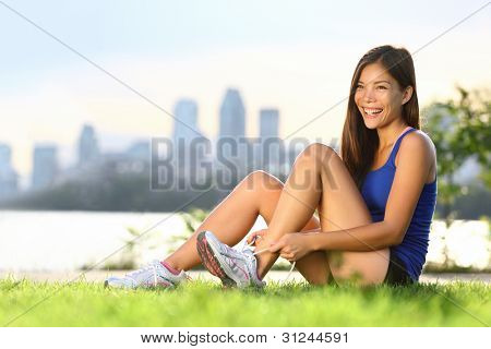 Woman runner happy tying running shoes before outdoor workout. Smiling mixed race Asian Caucasian sport fitness model training outside in city park in Montreal, Quebec, Canada.