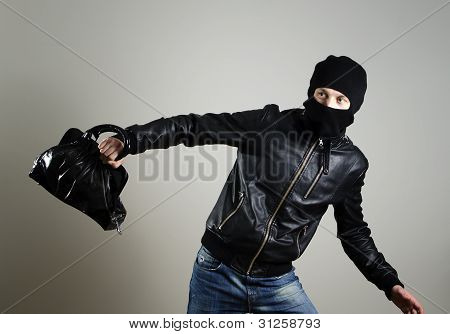 Portrait Of Running Male Burglar With A Handbag.