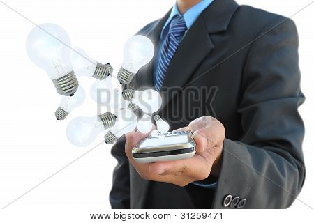 businessman hand holding mobile phone and light bulb