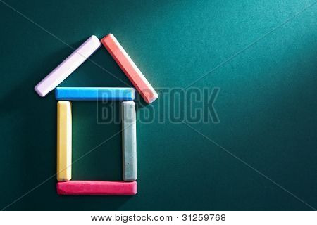 Close-up of colorful pieces of chalk put in form of house on blackboard