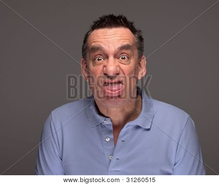 Man Pulling Face Sticking Out Tongue on Grey Background