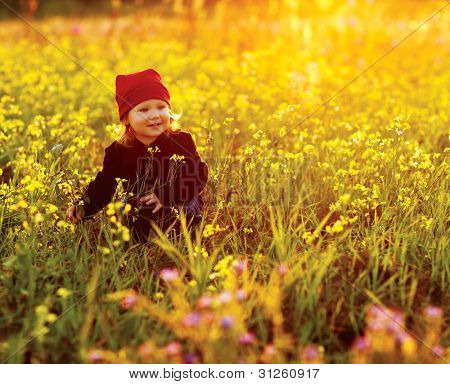 happy small girl with field flowers