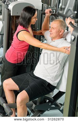 Fitness center personal trainer assist man exercise shoulder on machine