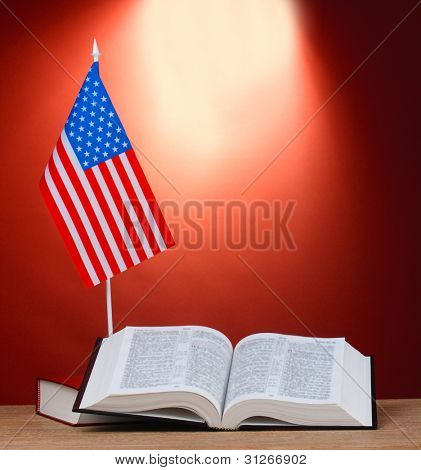 American flag on the stand and books on wooden table on red background