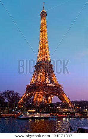 Eiffel Tower illuminated at night. View from the Seine quay. March 14 2012 in Paris France.