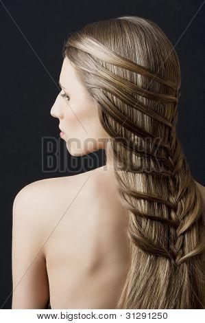 Longo cabelo e penteado da moda, ela parece para baixo à esquerda