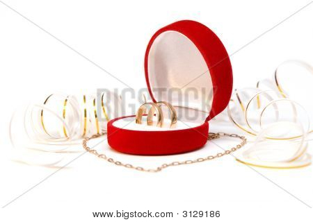 Close Up Of Wedding Bands And Gold Chain Looking Like Heart Over White Background
