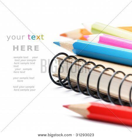 bunte Bleistifte und Notebook isolated over white