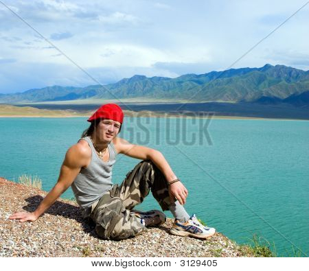 Boy Teens Sitting On A Stump By A Beautiful Lake With Green Water. Kazakhstan, Bortoguy (Series Spor