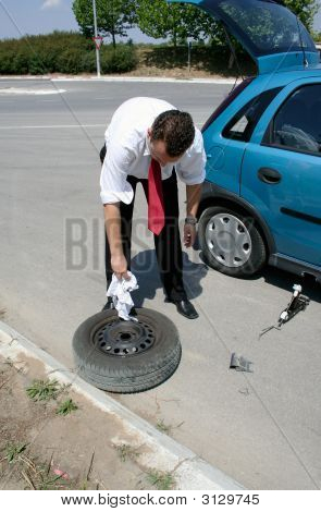 Businessman Changing A Tire