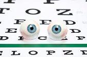 stock photo of snellen chart  - A pair of prosthetic eyeballs on a snellen eye chart - JPG