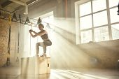 Working Out. Side View Of Beautiful Athletic Woman In Sportswear Training Legs At Gym. poster