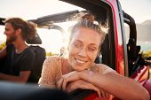 Millennial white couple on a road trip driving in open top car, women leaning on car door, close up poster
