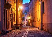 Narrow street of Old town with Night illumination. Czech Krumlov. Czech Republic. Shining lanterns a poster