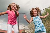 stock photo of bounce house  - Small cute children jumping on trampoline  - JPG