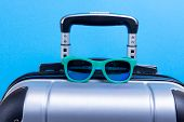 Suitcase Luggage For Hand Luggage And Sunglasses On A Blue Background. Concept Travel On Summer Vaca poster