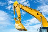 Yellow Backhoe With Hydraulic Piston Arm Against Blue Sky. Heavy Machine For Excavation In Construct poster