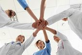 Team Of Medical Workers Holding Hands Together In Hospital, Bottom View. Unity Concept poster