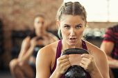 Portrait of concentrated young woman working out with kettlebell at gym. Closeup face of determined  poster