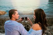 Romantic Romantic Couple Sitting With Wineglasses At Seaside At Sunset. Romantic Concept. poster