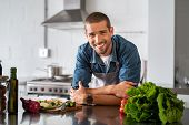 Handsome smiling young man leaning on kitchen counter with vegetables and looking at camera. Portrai poster