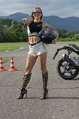 Beautiful, Slender Girl Shows The Key To The Motorcycle. Novice Driver Standing Next To A Motorcycle poster