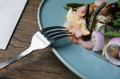 A Closeup Of A Fork With Impaled Shrimp On It. Delicious Salad With Shrimps On A Wooden Table. Shrim poster