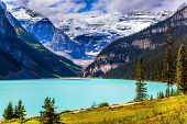 Travel to the Rocky Mountains of Canada. The lake with azure water is surrounded by mountains and fo poster