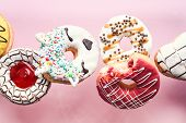 Various Decorated Doughnuts In Motion Falling On Pink Background. Sweet And Colourful Donuts Flying  poster